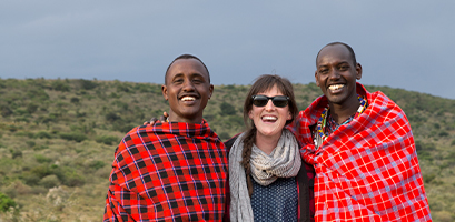 Local community members wearing shuka blankets and traveller posing for a picture in the savanna