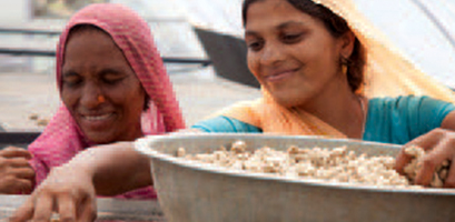 Local women smiling and picking food from a bowl