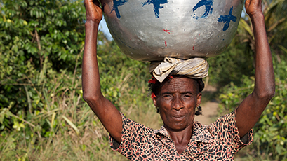 A women walks with a bowl of water balanced on her head