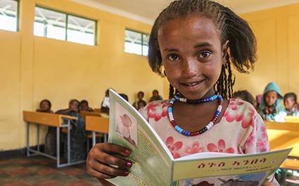 A girl reading in front of her class
