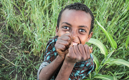 A boy laughing in a field