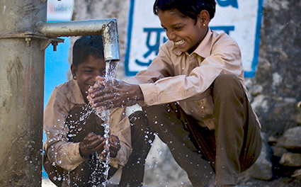 Boys using a water pump in India