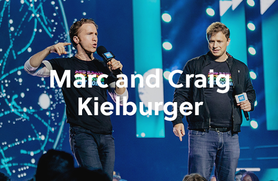 Craig and Marc Kielburger talking at a WE Day event