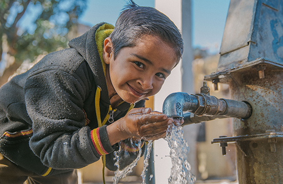 Local boy drinking from tap in India