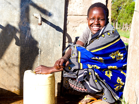Local youth collecting water from water tap in Kenya