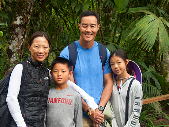 Family posing for picture in the rainforest