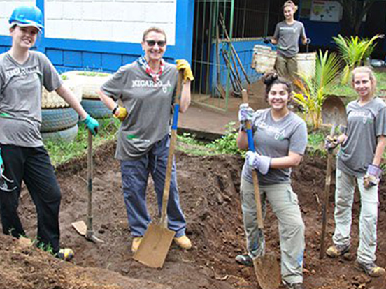 Xavier students hold shovels at a build site in Nicaragua.