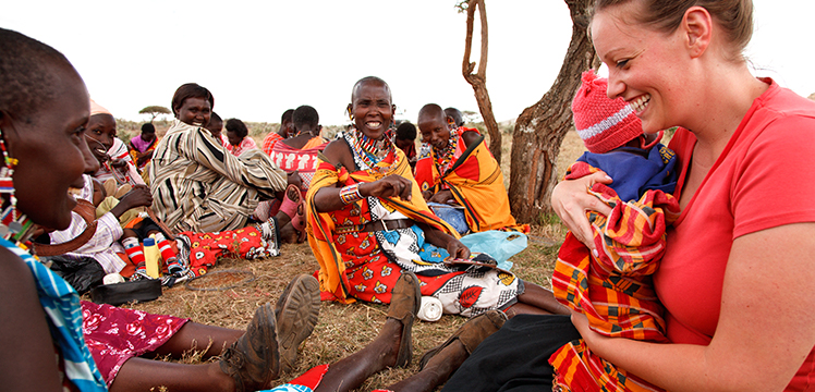Traveller talking with local women sitting under acacia trees