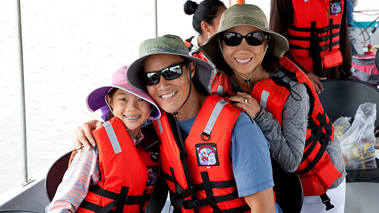 Family of travelers posing for a picture on a boat