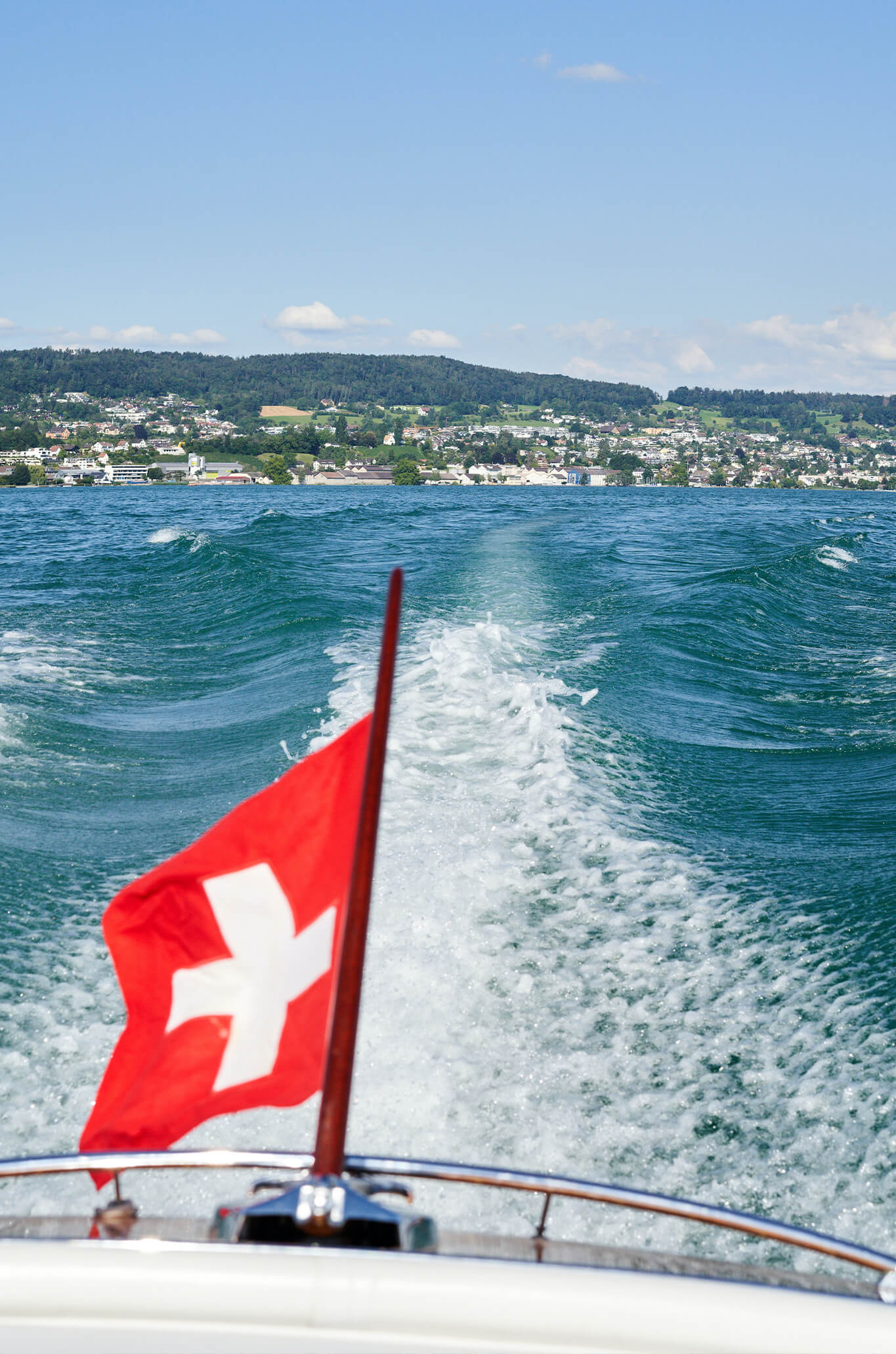flag waving off a boat on lake zurich