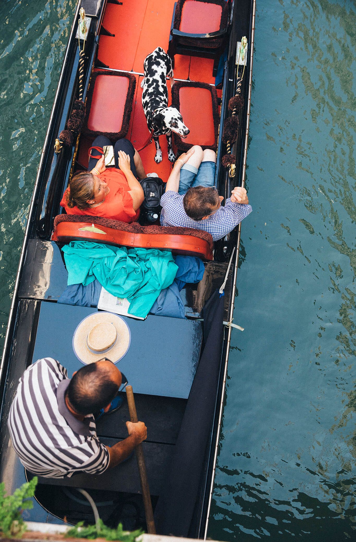 A couple riding in a gondola with a Dalmatian in Venice, Italy