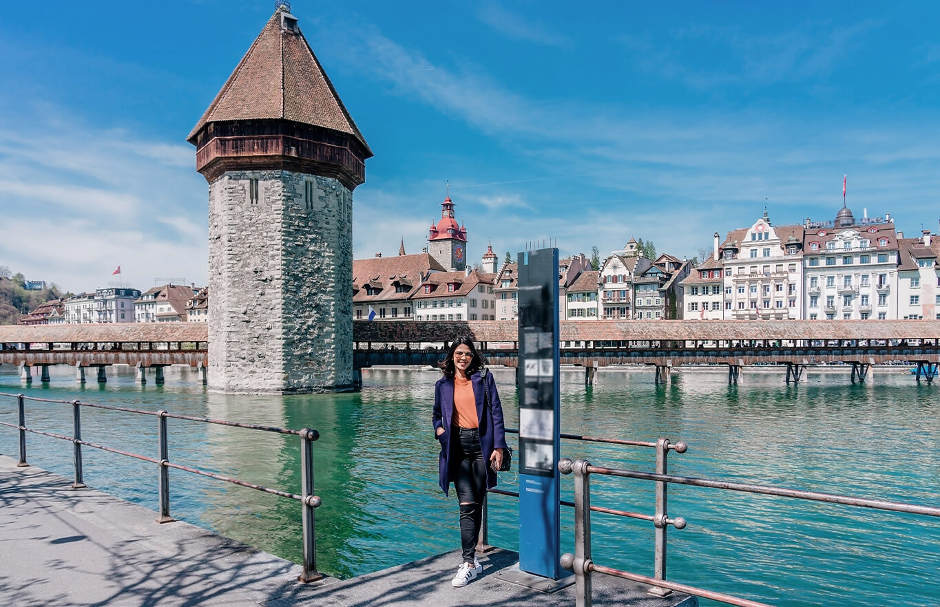 woman standing in front of the chapel bridge in lucerne