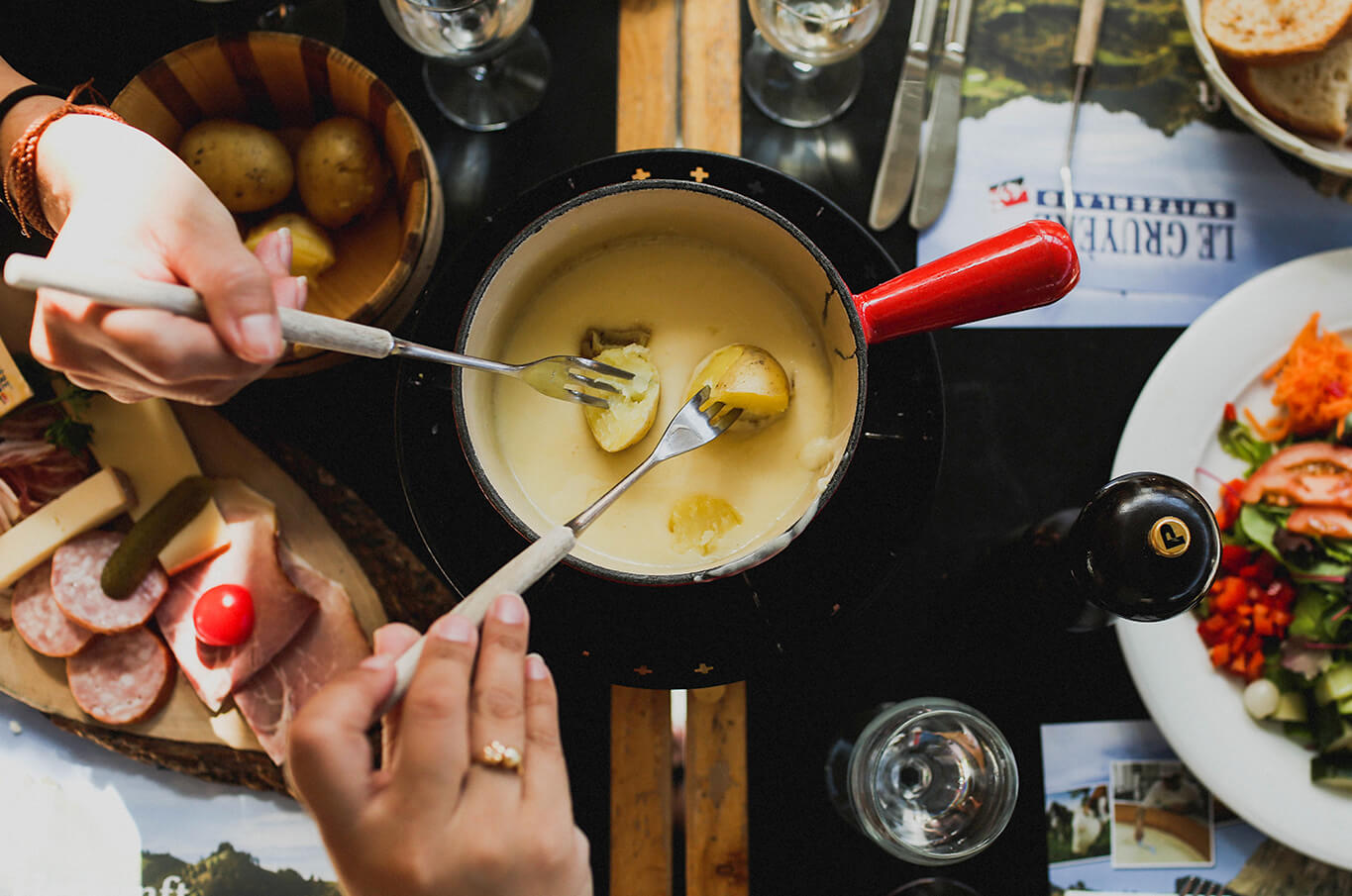2 hands with forks dipping potatoes into fondue