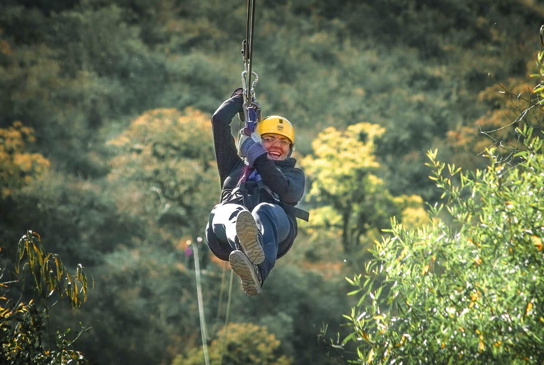 woman ziplining over the rainforest