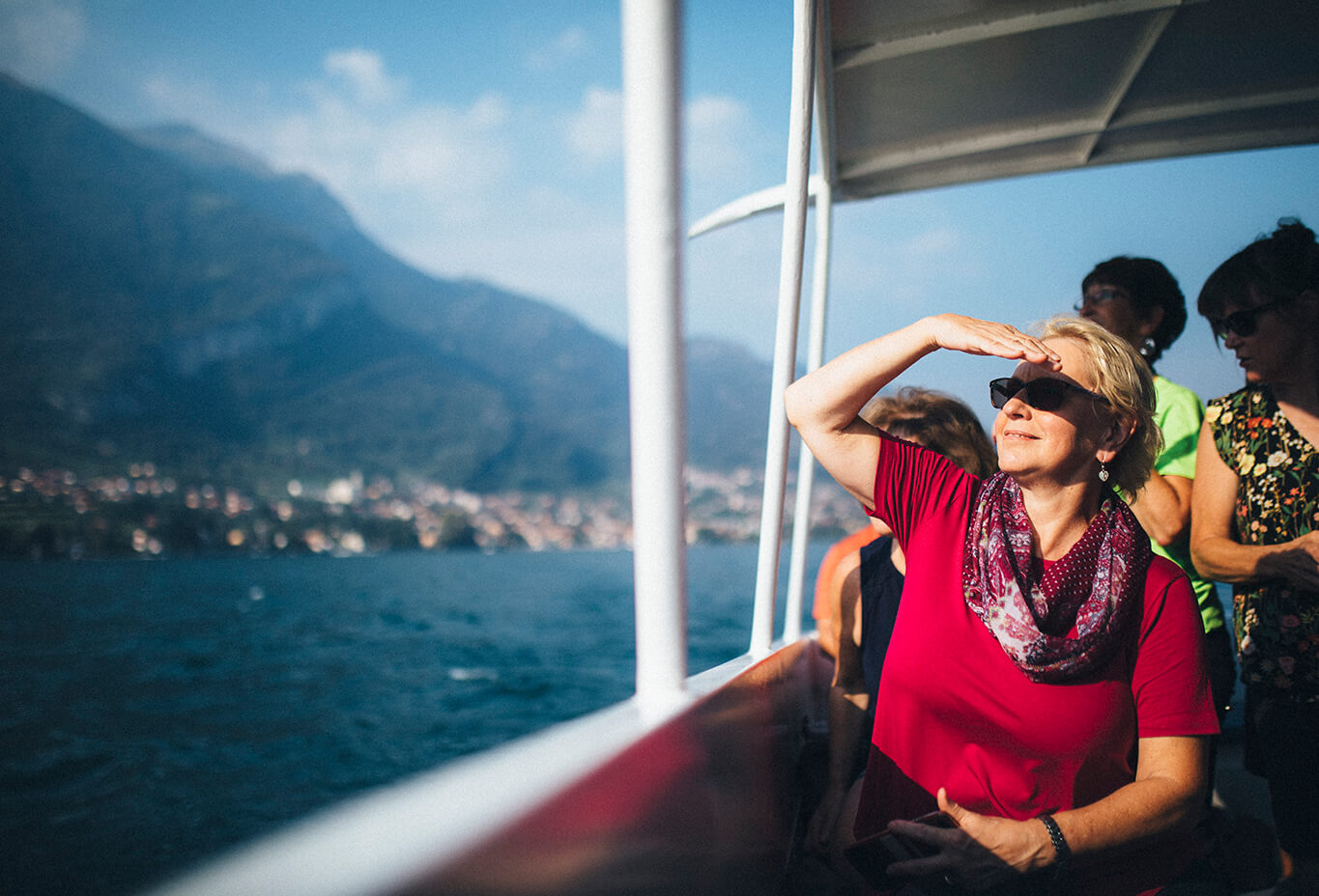 woman blocking the sun with her hand while riding on a boat