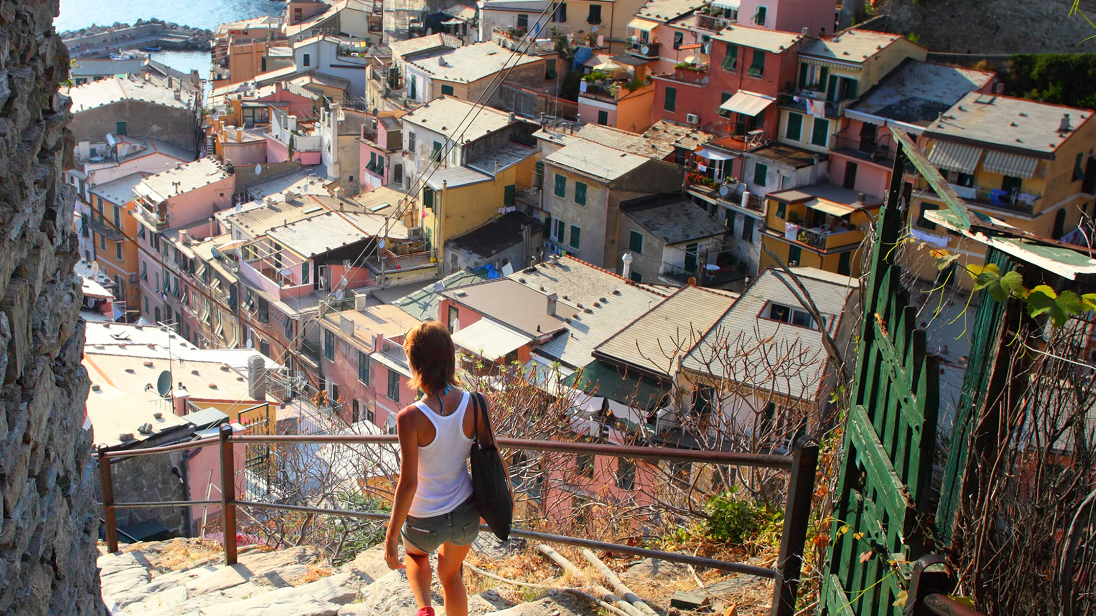 woman walking down stairs overlooking the town of vernazza