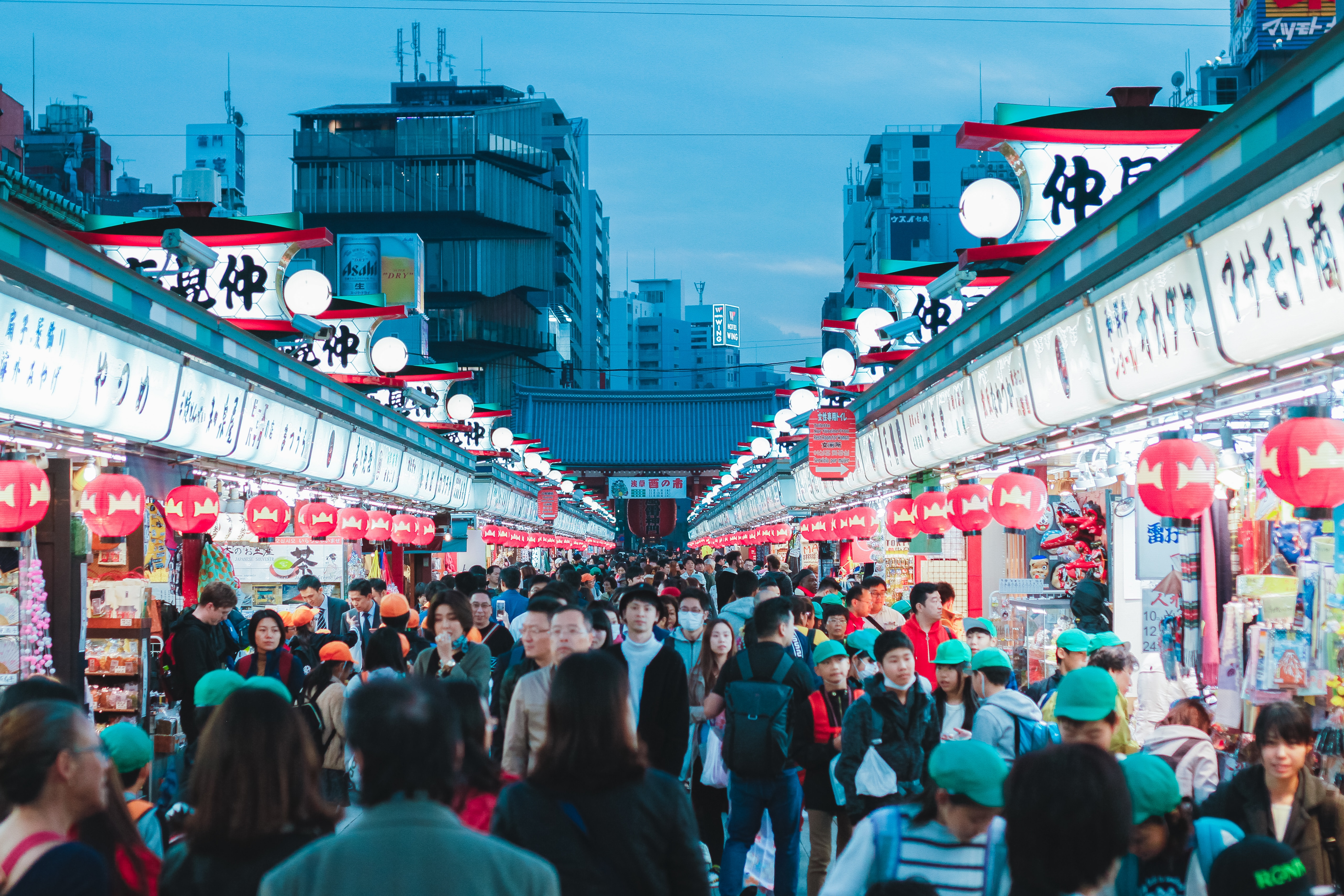 crowds of people walking around outdoor market in tokyo at night