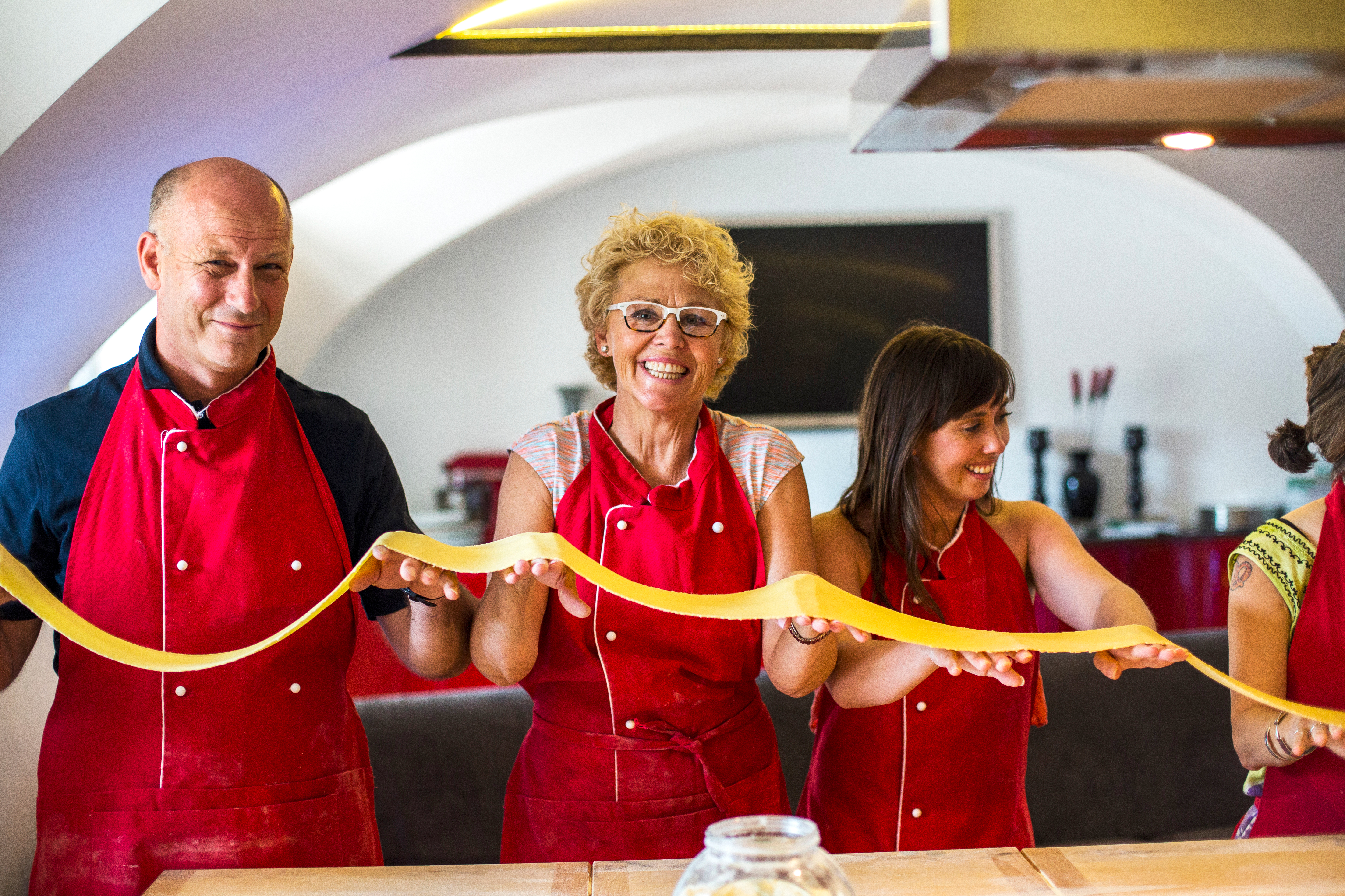people holding fresh pasta at cooking class in italy