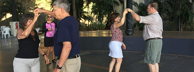 two couples dancing salsa together