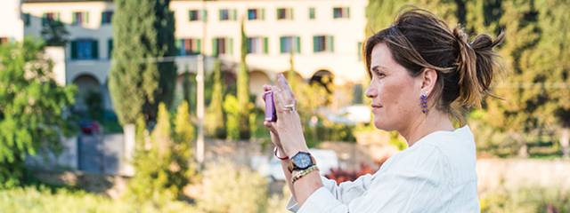 woman holding an iphone taking a photo in fiesole italy