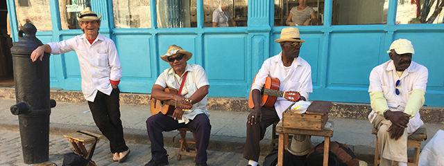 four cuban musicians sitting outside a bright blue building