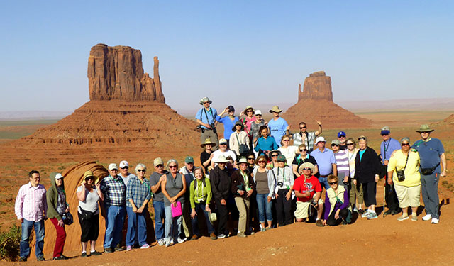 group tour of travelers posing for a picture in monument valley in colorado