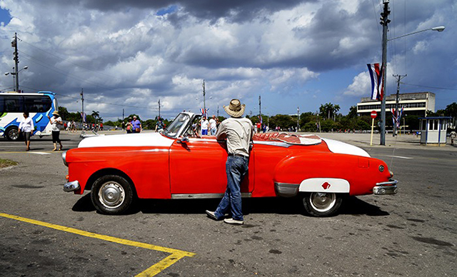 man facing away from camera leaning up against bright red and white car