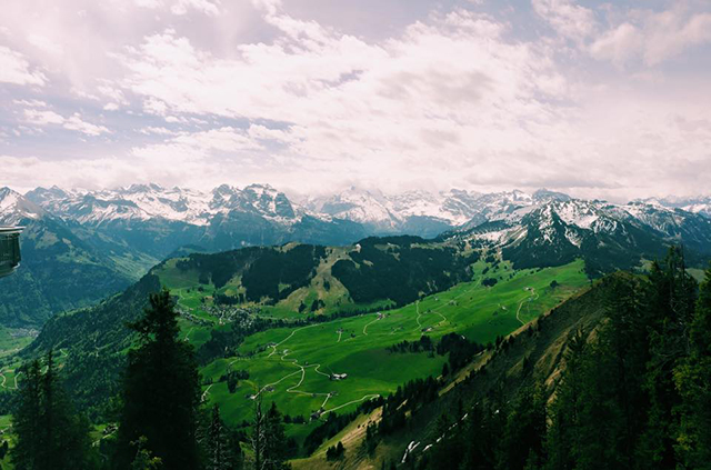lush green mountain range surrounded by snow capped mountains in switzerland