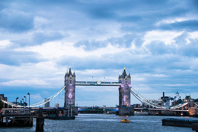tower bridge in london lit up with purple lights on a cloudy day