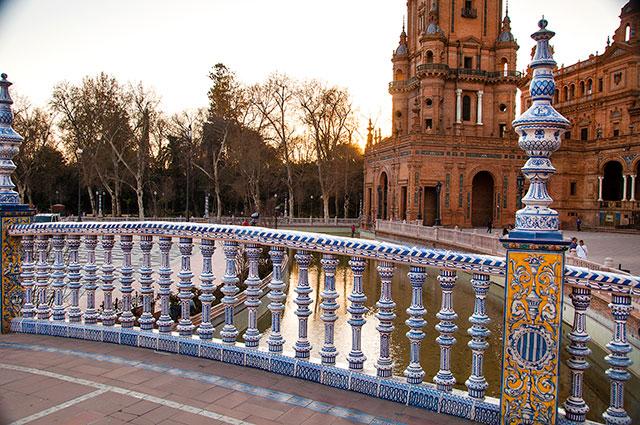blue and white marble bridge over a river in the plaza de espana in seville