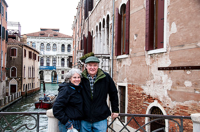 couple standing on a bridge over a canal in venice italy