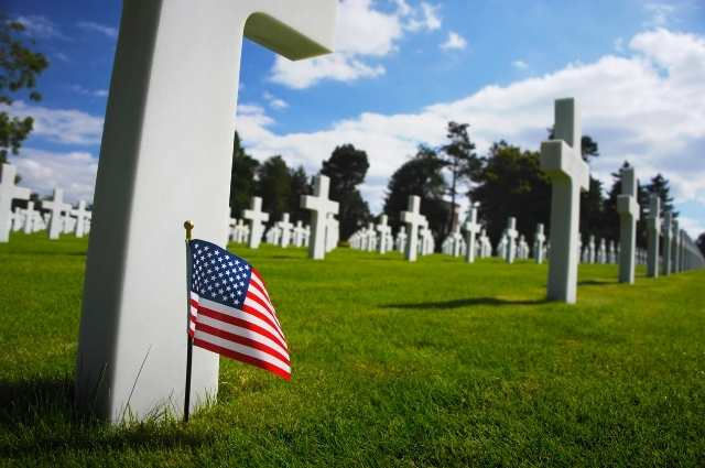 american flag in front of a gravestone at the Henri-Chapelle American Cemetery in belgium
