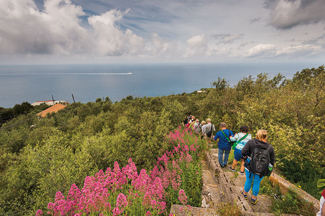 group of travelers walking down wooden trail in the amalfi coast in italy