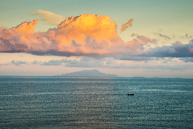 boat floating in ocean with silhouette of mountain in background during sunset