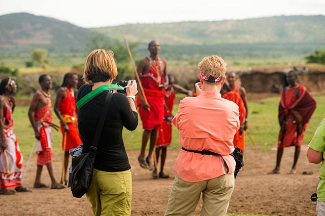 two travelers taking photos of masai mara tribe