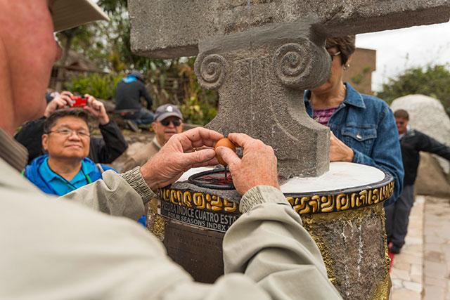 man cracking an egg at the equator in ecuador