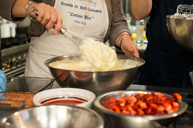 woman whisking whipped cream during cooking class in florence
