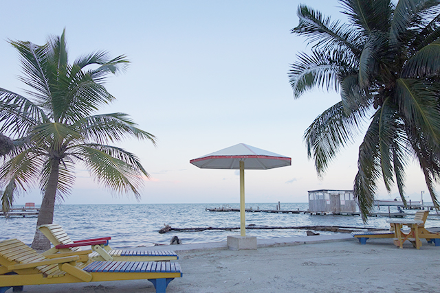 beach chairs and umbrella on beach in belize at sunset