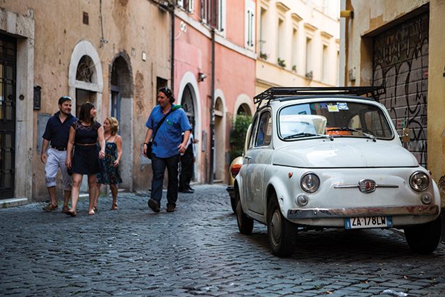 group walking past old white fiat car on a street in rome italy