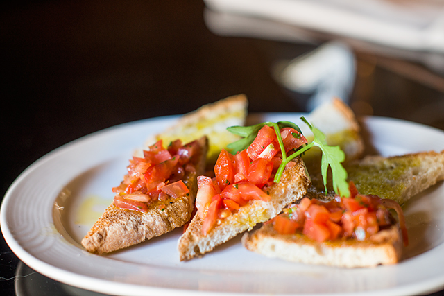 three pieces of bruschetta on white dish