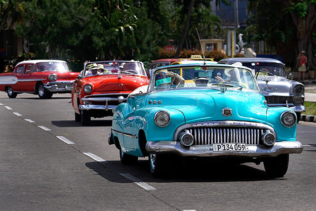 people driving in classic old cars on street in cuba