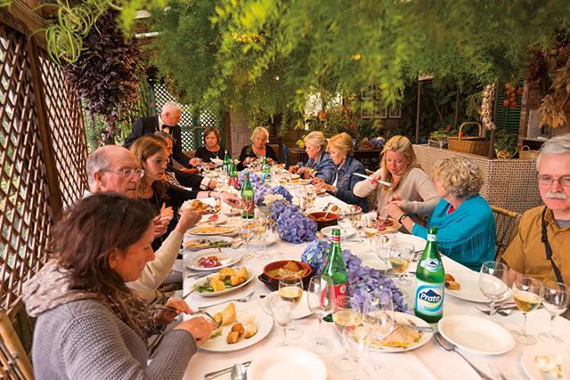 group of travelers enjoying dinner at italian farmhouse