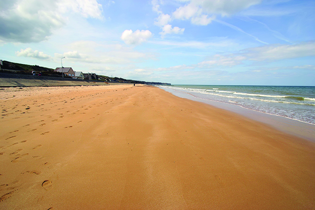 omaha beach in normandy on a partially cloudy day