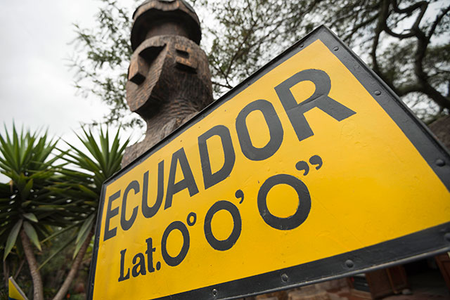 yellow and black sign with coordinates of ecuador
