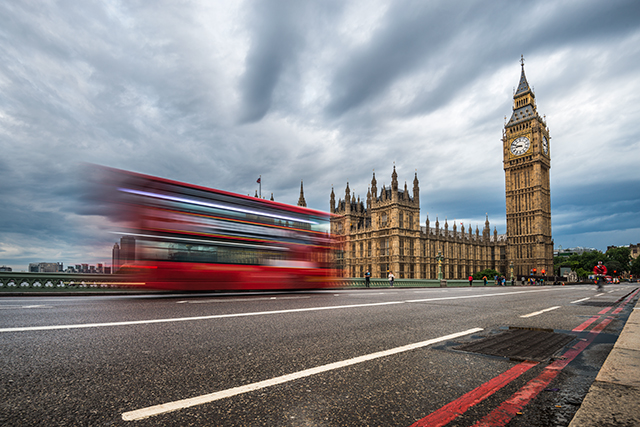 red double decker bus driving past big ben in london england