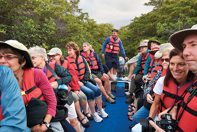 group of travelers wearing life vests sitting on a boat