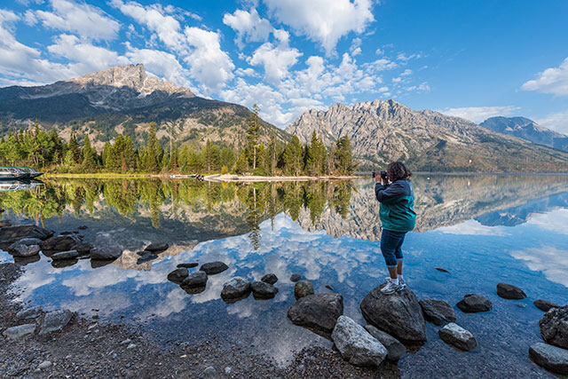 woman standing on edge of lake in national park taking a picture