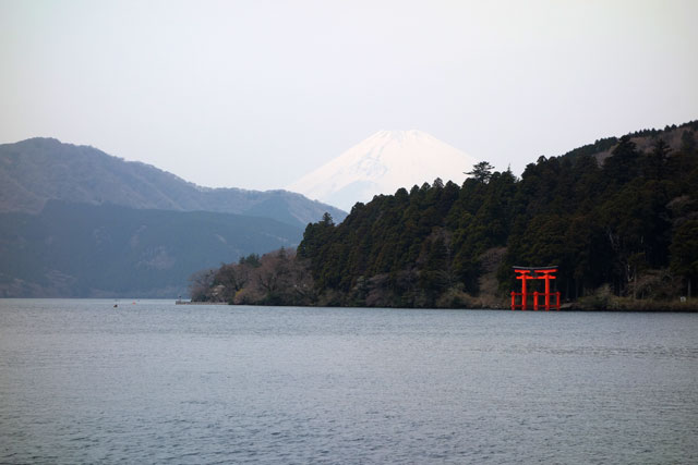 water of lake looking at the red shinto shrine in japan