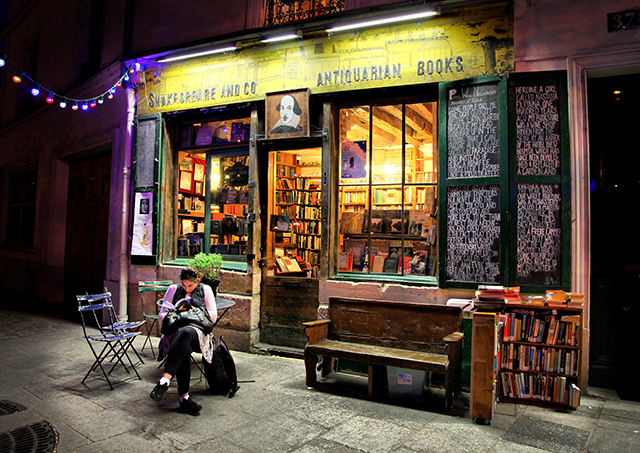 woman sitting outside of famous bookstore in paris