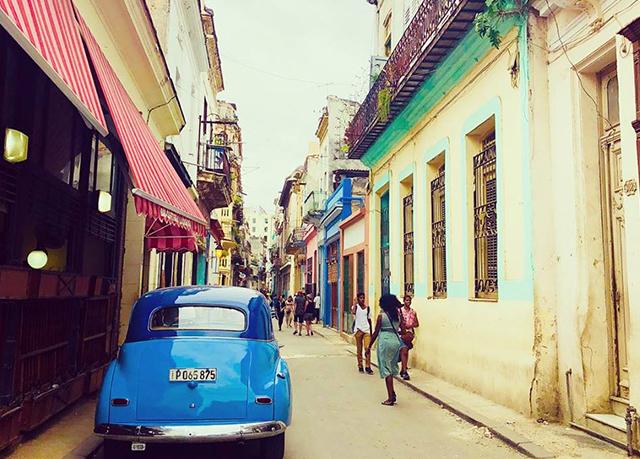 people walking down the street in havana past a blue car